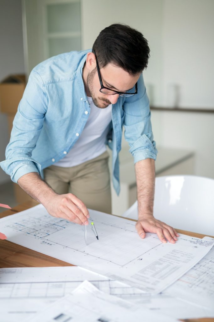 Architect working on plans at home office table